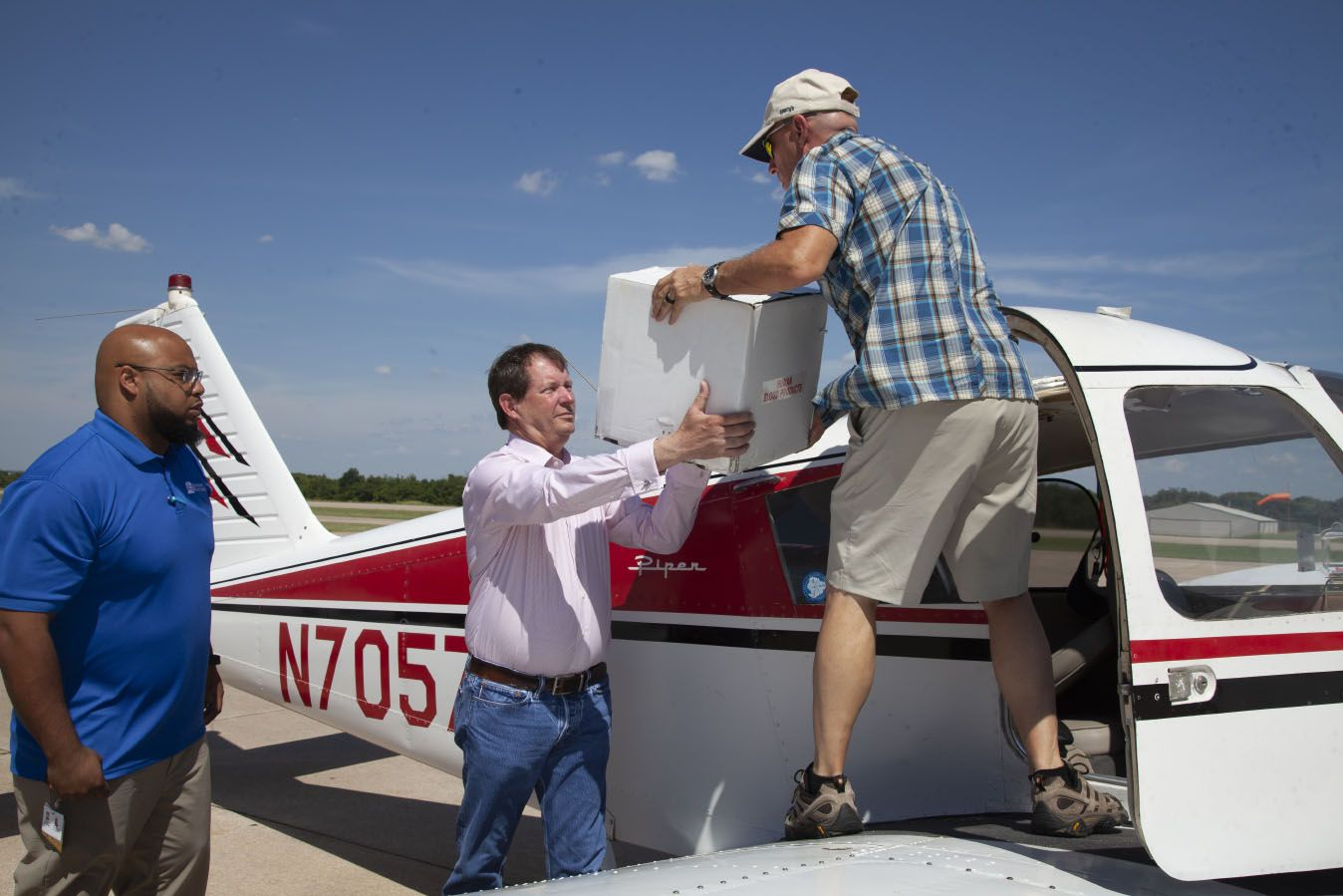 Carvin Brown and Jerry Hunter help load Clark Southard's airplane as he prepares for a Flights For Life mission.